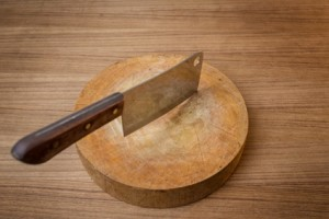 Knife on a wooden butcher on wooden background.