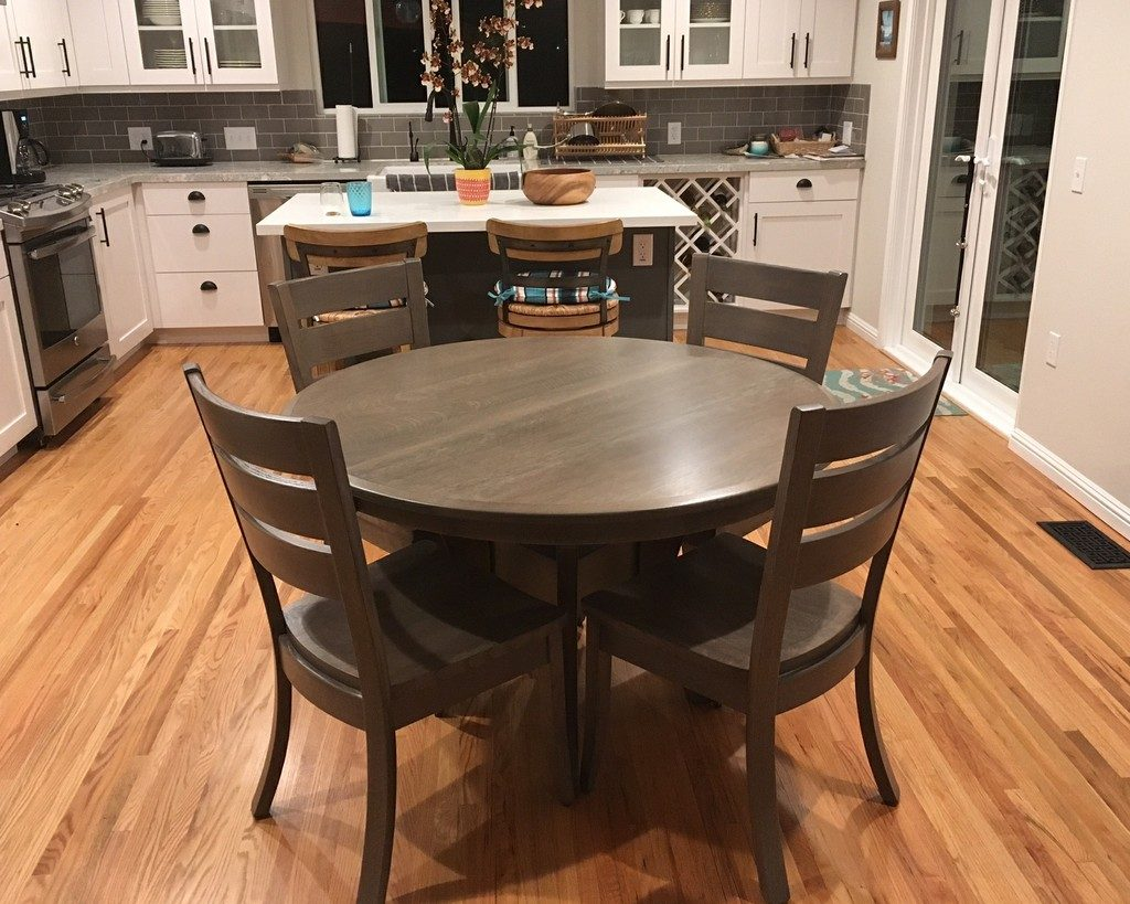 The Imperial Single Pedestal Dining Table in its round state without leaves, and the Savannah Dining Chairs, in quarter-sawn white oak with Windswept Glazed stain from Amish Furniture Factory
