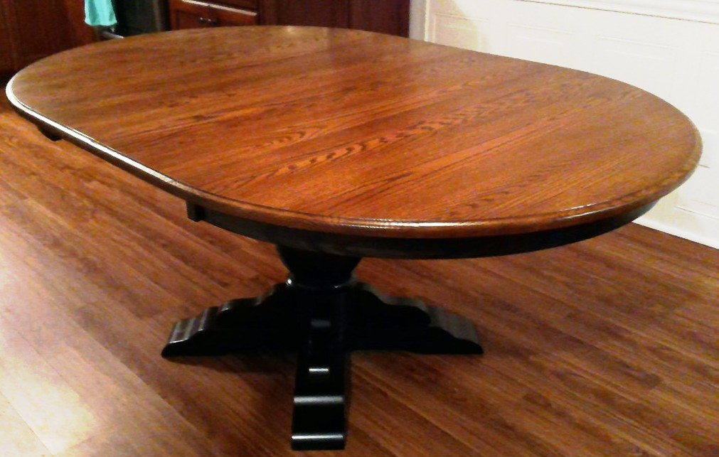 Albany Single Pedestal Dining Table is normally round but it accepts leaves. This table is oak with an acorn and ebony two-tone stain.