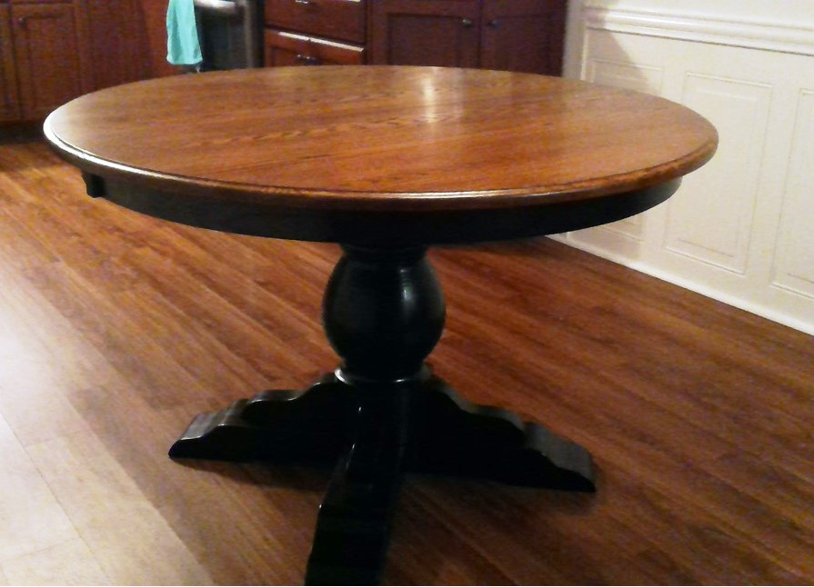 A round Albany Single Pedestal Dining Table in oak with an acorn-stained top and an ebony-stained base.