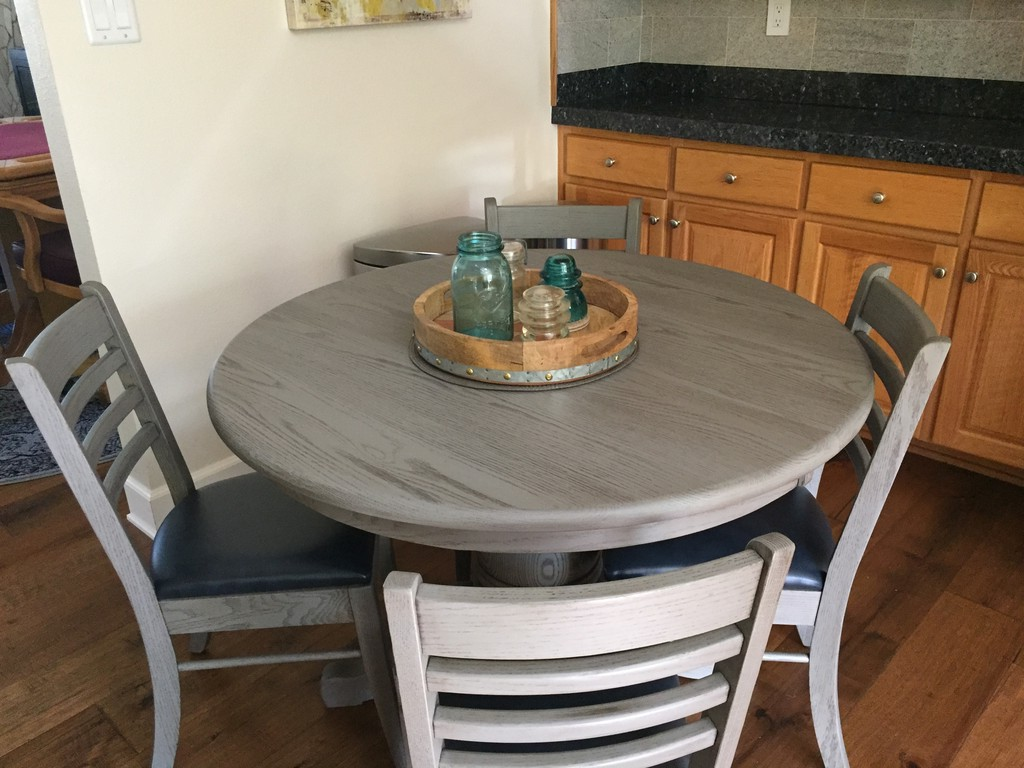 This round pedestal and Brady Dining Chairs are in Chelsea Gray glazed finish and the chairs are upholstered in Storm. But the table has a surprise: the Split Pedestal Dining Table extend from a single pedestal table to a triple pedestal capable of seating 18!—Amish Furniture Factory