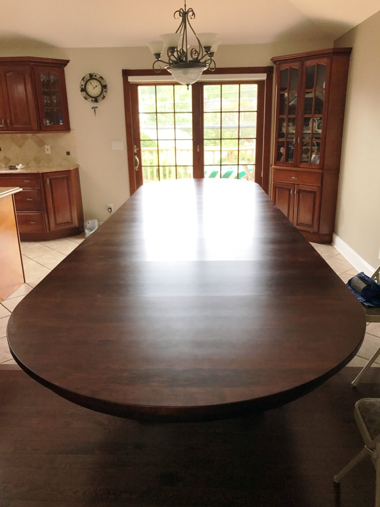 A Monteray Split Pedestal Dining Table in hard maple with Burnt Umber stain and a lot of leaves in—Amish Furniture Factory