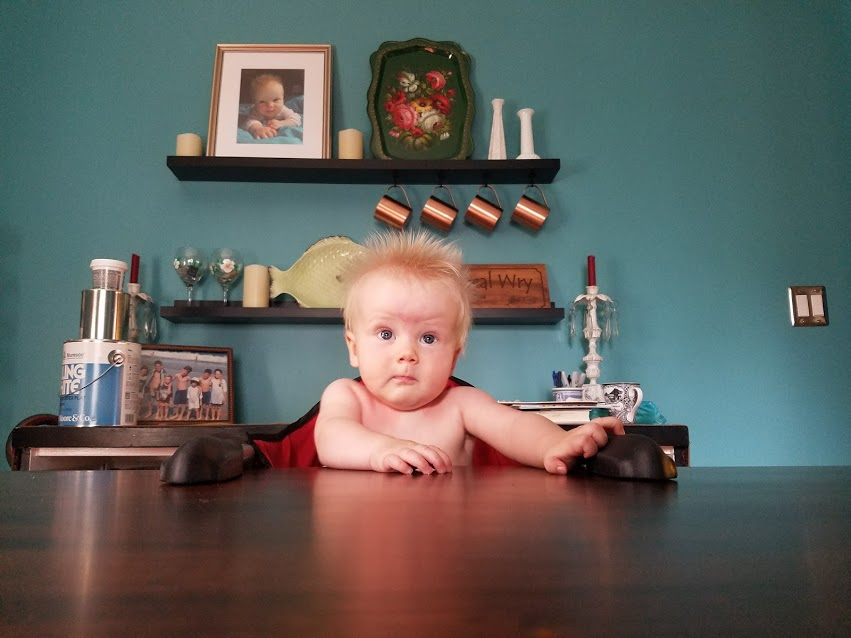 A baby sitting at a Laurie's Leg Dining Table from Amish Furniture Factory