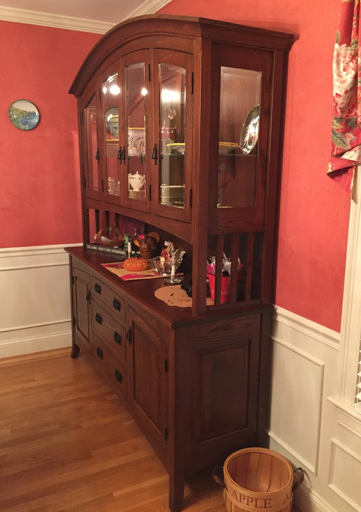 The Cambria Hutch from Amish Furniture Factory in oak with Old World Mission stain in a red dining room with floor-to-table-height white panels and honey colored hardwood floor