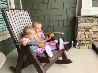 Two little girls on a Poly Vinyl Comfort Rocker in color weatherwood with chestnut brown supports