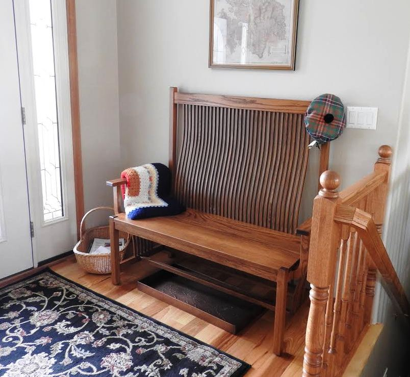 Midway Mission Bench in Oak with Malaguania Stain between an outside door and the top of a stair banister with a picture hanging above