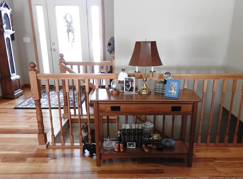 This sofa table is up against an indoor horizontal railing over a stairwell. FVA8157 FVST-WL West Lake Open Sofa Table – Cherry w/Baywood Stain, D527 Blk hardware from Amish Furniture Factory