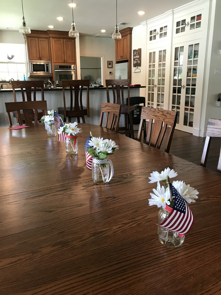 Mason Double Pedestal Dining Table and Gatlinburg Dining Chairs and Bar Stools in oak with New Carrington stain, from Amish Furniture Factory. Mini jar bouquets with daisies and American flags run along the center of the oblong table.