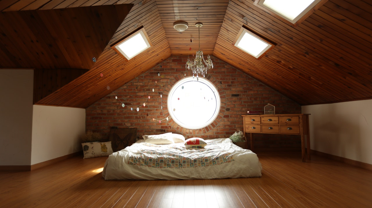 To brighten an attic bedroom, avoid blocking light sources, and carefully plan to place a mirror somewhere it fits.