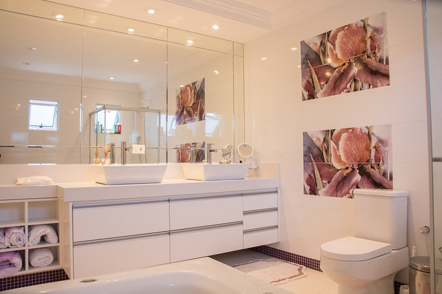An almost all-white bathroom with floor-to-ceiling tiles and wall-to-wall, counter-to-ceiling mirrors
