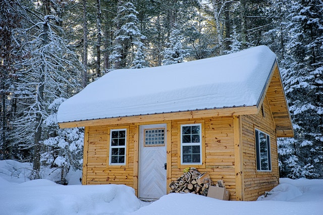 Tiny wooden cabin with pointed roof covered in snow in winter