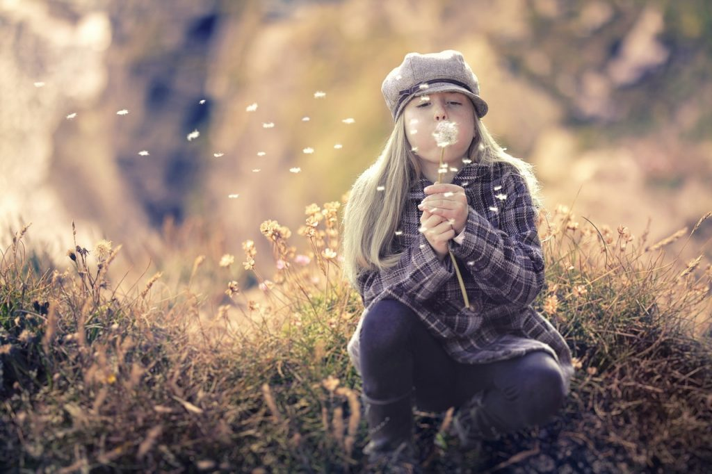 A girl crouching in dry autumn grass blowing dandelion seeds