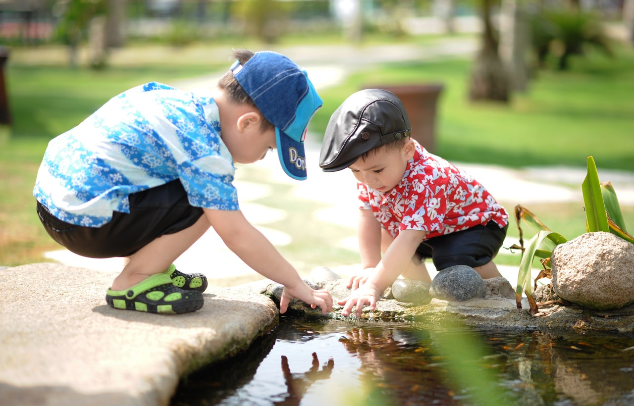 Two small boys playing with water in a shallow garden pond.