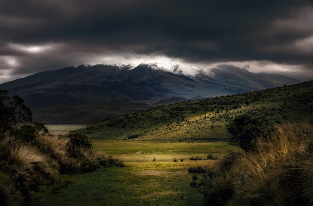 A field in the foothills of a mountain with dark storm clouds above