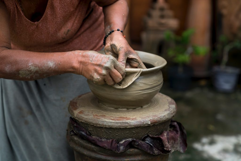 A woman working pottery in a courtyard