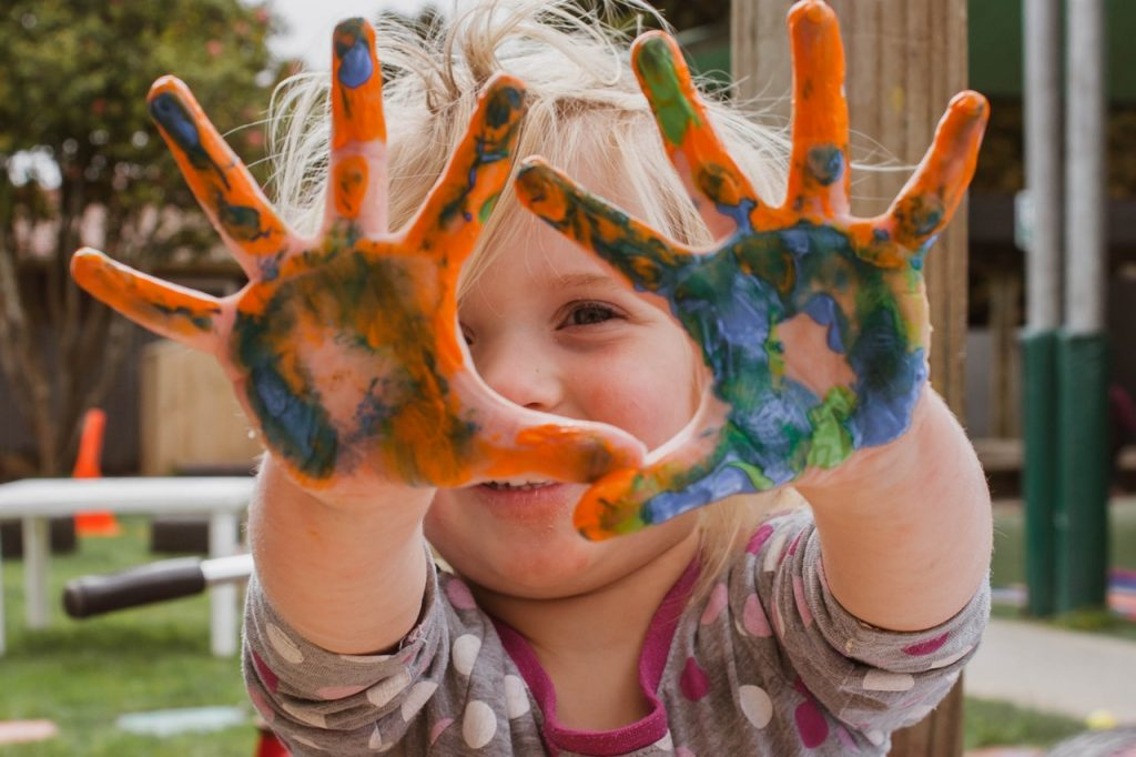 A kid holding up her hands showing many colors of paint all over them.
