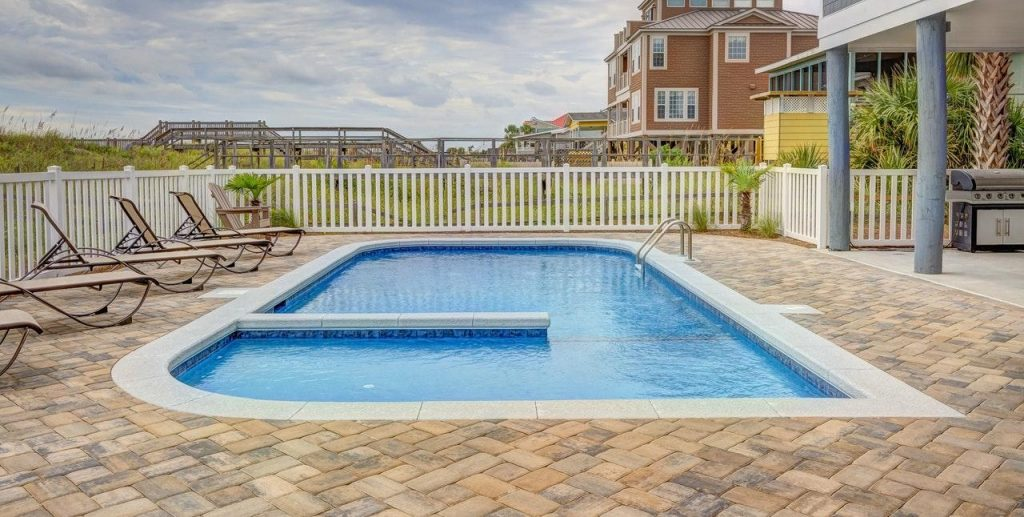 A pool in a brick patio with lounge chairs