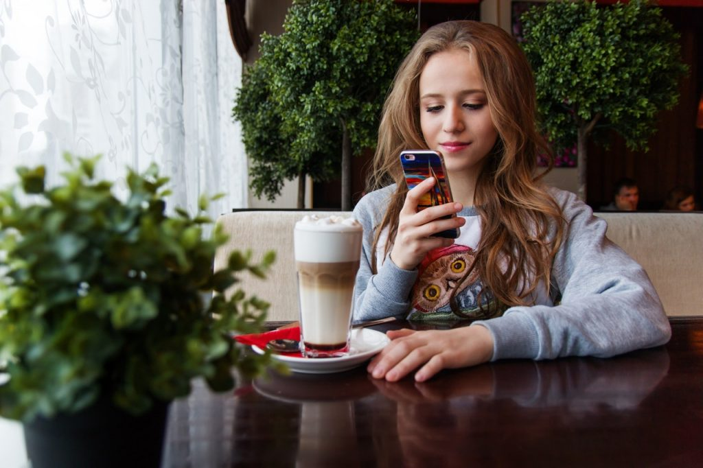 A teenage girl taking a picture of her beverage in a cafe